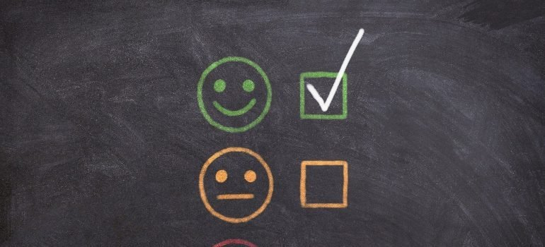 Smileys rating customer satisfaction on a chalkboard.