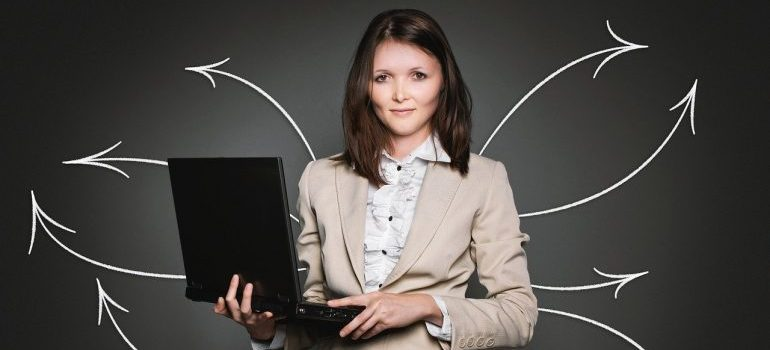 A woman holding a laptop.