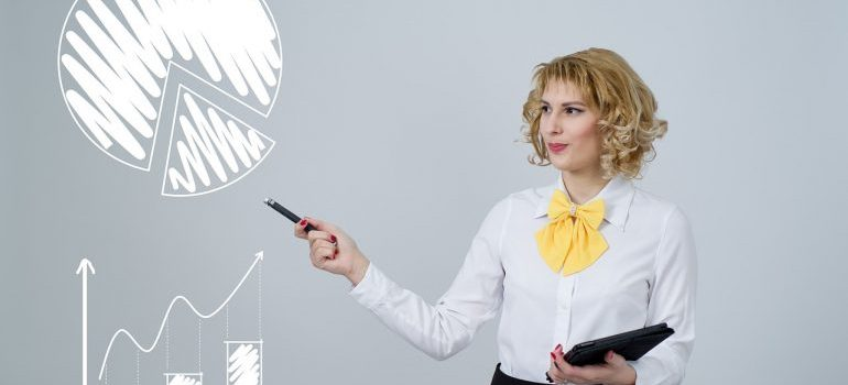A woman pointing at a chart of PLM adoption, segments and vendors.