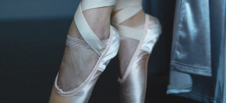 Woman putting on ballet shoes.